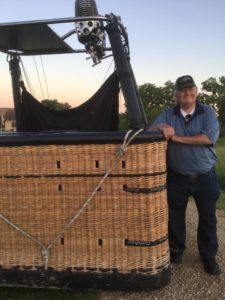 John stands next to wicker basket of hot air balloon