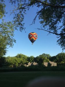 Hot air balloon taking off into blue sky
