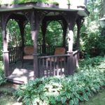 a brown gazebo is surrounded by green plants. Two chairs sit in the gazebo