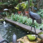 a metal crane bird stands above a rectangular water fountain