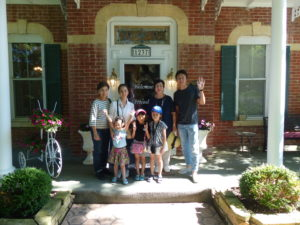 Family of seven from Japan wave goodbye in front of the Cloran Mansion