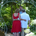 Couple faces a minister for their renewal of vows under a heart on the grounds of the Cloran Mansion