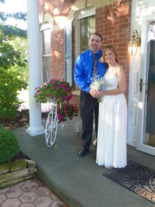 Michelle Jordan with bouquet stands with new husband Dennis in front of the Cloran Mansion and a bicycle planter