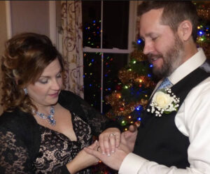 Amanda and Brian exchange rings in front of the Christmas tree in the dining room